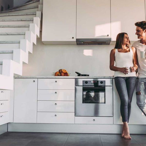 happy-couple-standing-in-front-modern-splashback (745090438)